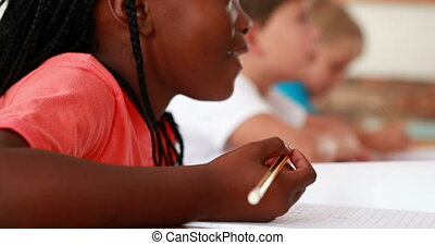 Little girl writing during class in elementary school