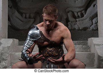 Gladiator in armour sitting on steps of ancient temple and...