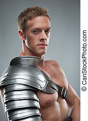 Closeup portrait of Gladiator in armour over grey background...