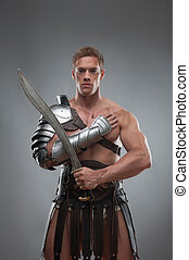 Gladiator in armour posing with sword over grey background -...