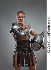 Gladiator in armour posing with helmet over grey background...