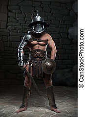 Gladiator in helmet and armour holding sword - Full length...