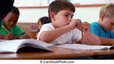 Little boy writing during class in elementary school