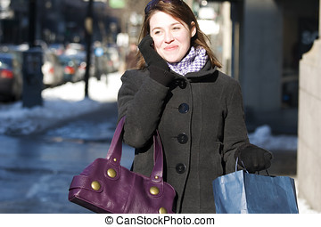 Woman walking down street on cell phone with shopping bags