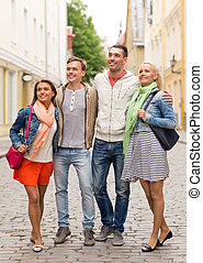 group of smiling friends walking in the city - friendship,...