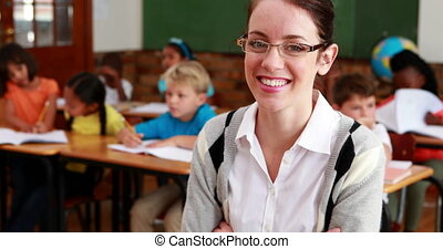Pretty teacher smiling at camera at top of classroom in...