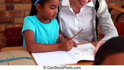 Teacher helping a little girl