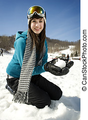Young girl playing in snow at ski resort