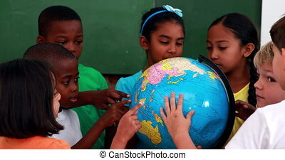 Pupils looking at the globe in classroom in elementary...
