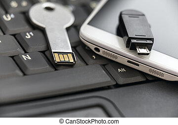USB key and smartphone with micro USB flash drive on laptop...
