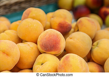 Crop of Peaches - Pile of tasty, orange peaches at a market...