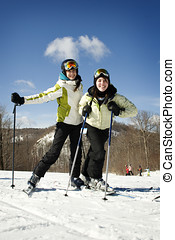 Two young girls skiing together on beautiful day