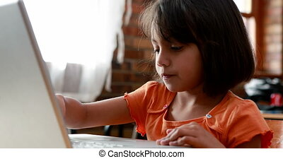 Girl using laptop in classroom - Little girl using laptop in...
