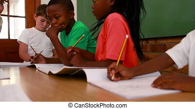 Pupils all working at the same desk in classroom in...