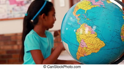 Girl looking at globe and writing - Little girl looking at...