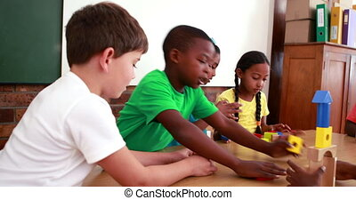 Pupils playing with building blocks in classroom in...