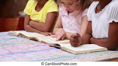 Cute pupils reading books at desk in elementary school