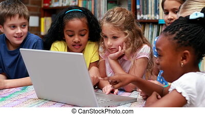 Pupils using the laptop together in the library in...