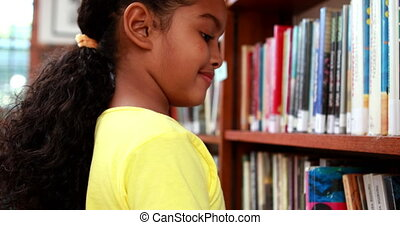 Little girl smiling at camera in the library in elementary...