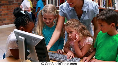 Pupils looking at the computer in library with their teacher...