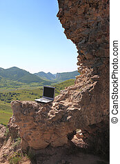 Laptop outdoors - Image of a laptop outdoors on a rocky wall...