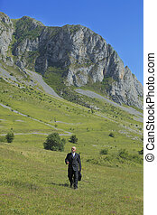 Businessman outdoors - Businessman walking in a mountaineous...