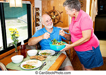RV Seniors - Serving Salad - Senior couple enjoying a...