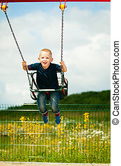 Little blonde boy child having fun on a swing outdoor -...