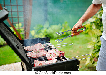 Man at barbecue grill preparing meat for a garden party
