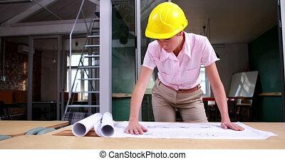 Architect studying blueprints - Focused architect studying...