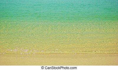 Warm sea surf with clear water and golden sand