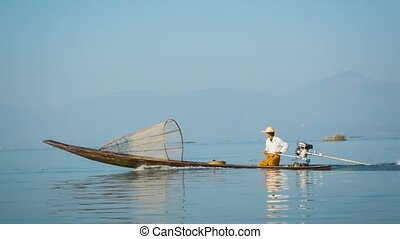 Local fisherman is moving quickly on the boat with a modern engine. Inle Lake, Myanmar