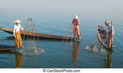 Village fishermen on traditional boats with fish traps. Inle...