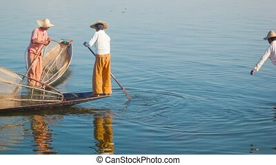 Local fishermen on boats in between fishing Inle Lake,...