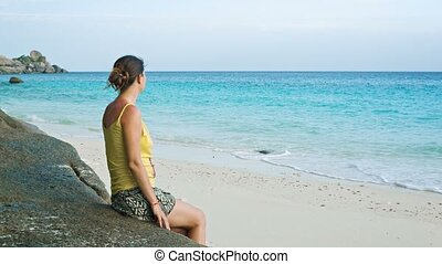 Woman sitting on the sea shore - Video 1080p - Woman sitting...