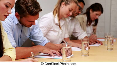 Business team taking notes - Casual business team taking...