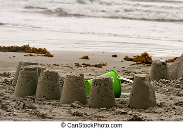Sand Pail - Unfinished sand castle at beach with bright...