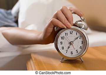 turn off alarm clock - Closeup on female hand reaching to...