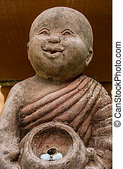 monk statue hold the rock with smile face