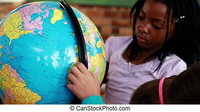 Cute pupils looking at the globe in classroom in elementary...