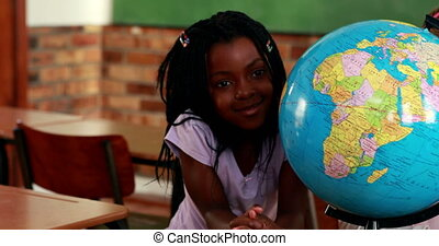 Cute pupils smiling around a globe in classroom in...