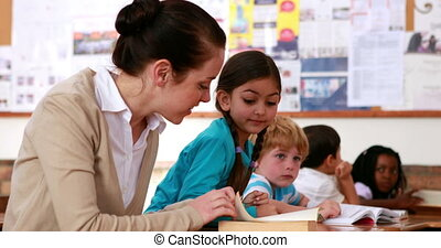 Teacher helping a girl with reading - Teacher helping a...