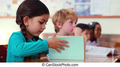 Cute pupil smiling at camera at her desk in classroom in...