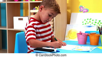 Little boy colouring in classroom