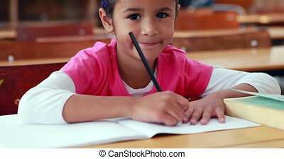 Cute little girl colouring in book in classroom smiling at...