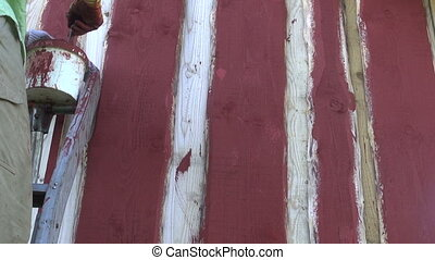 paint new farm barn wooden wall with paintbrush in red