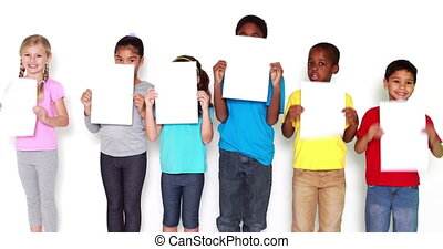 Children covering face with paper
