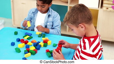 Cute little boys playing with building blocks at table in...