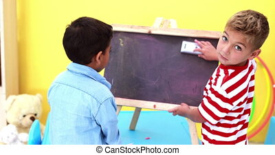 Cute little boys wiping and knocking over mini chalkboard in...