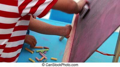 Cute little boys wiping down mini chalkboard in playschool